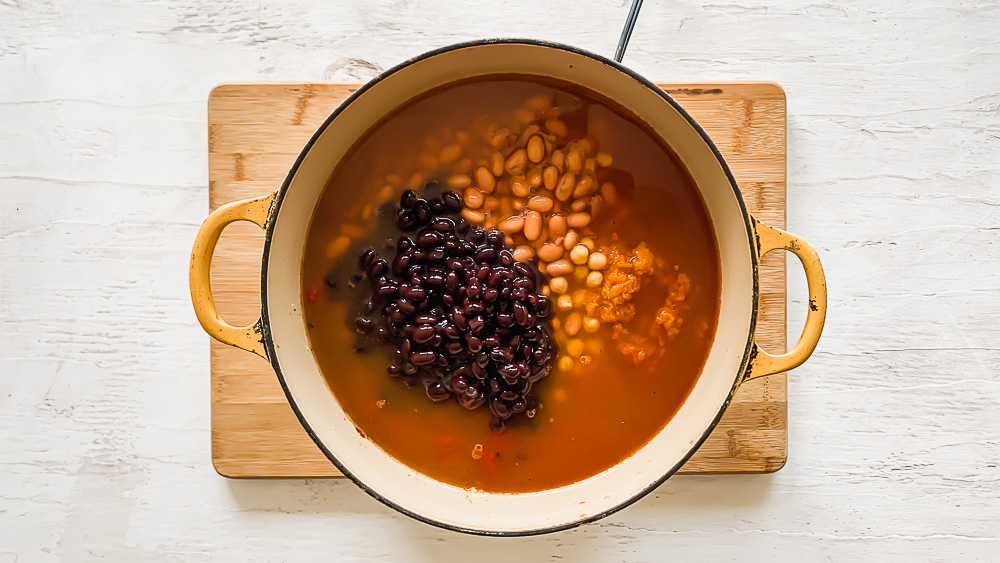 black beans, pinto beans, pumpkin, and chicken broth in a dutch oven