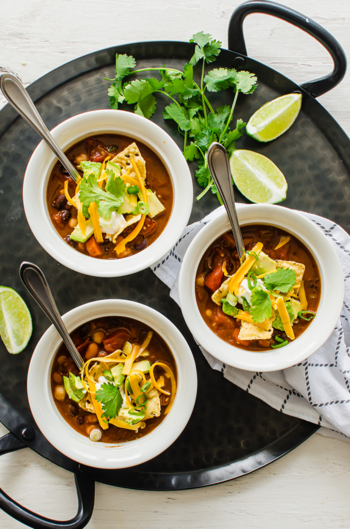 3 bowls of chili with toppings like tortilla chips, avocado, cilantro, lime wedges, and cheese