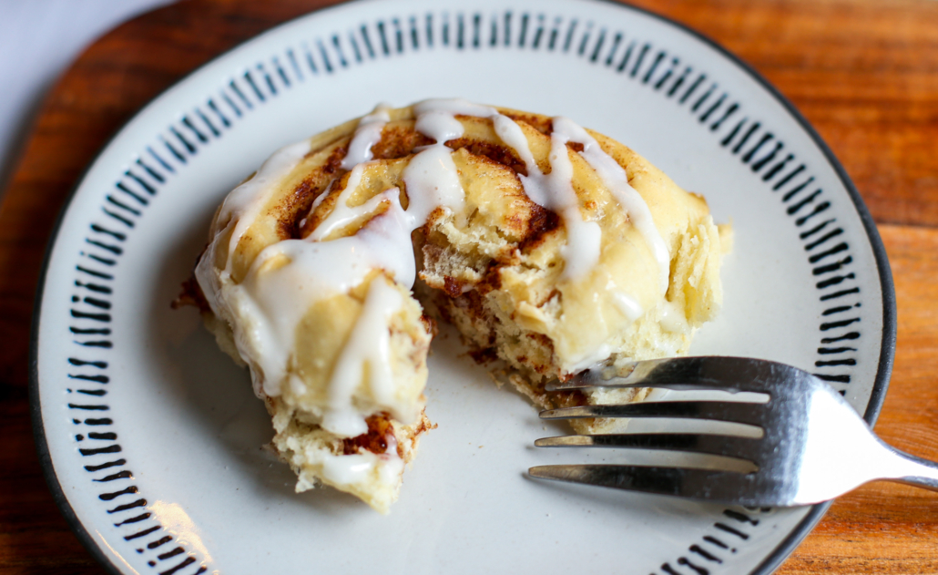 Baked cinnamon roll being cut into