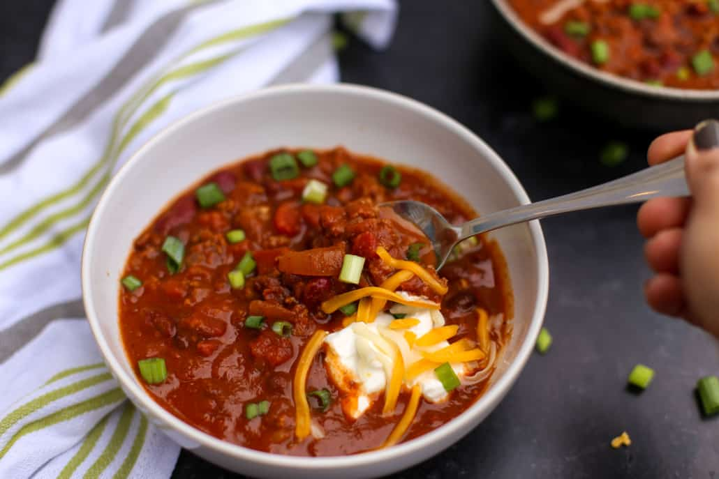 A spoon scooping chili out of a bowl
